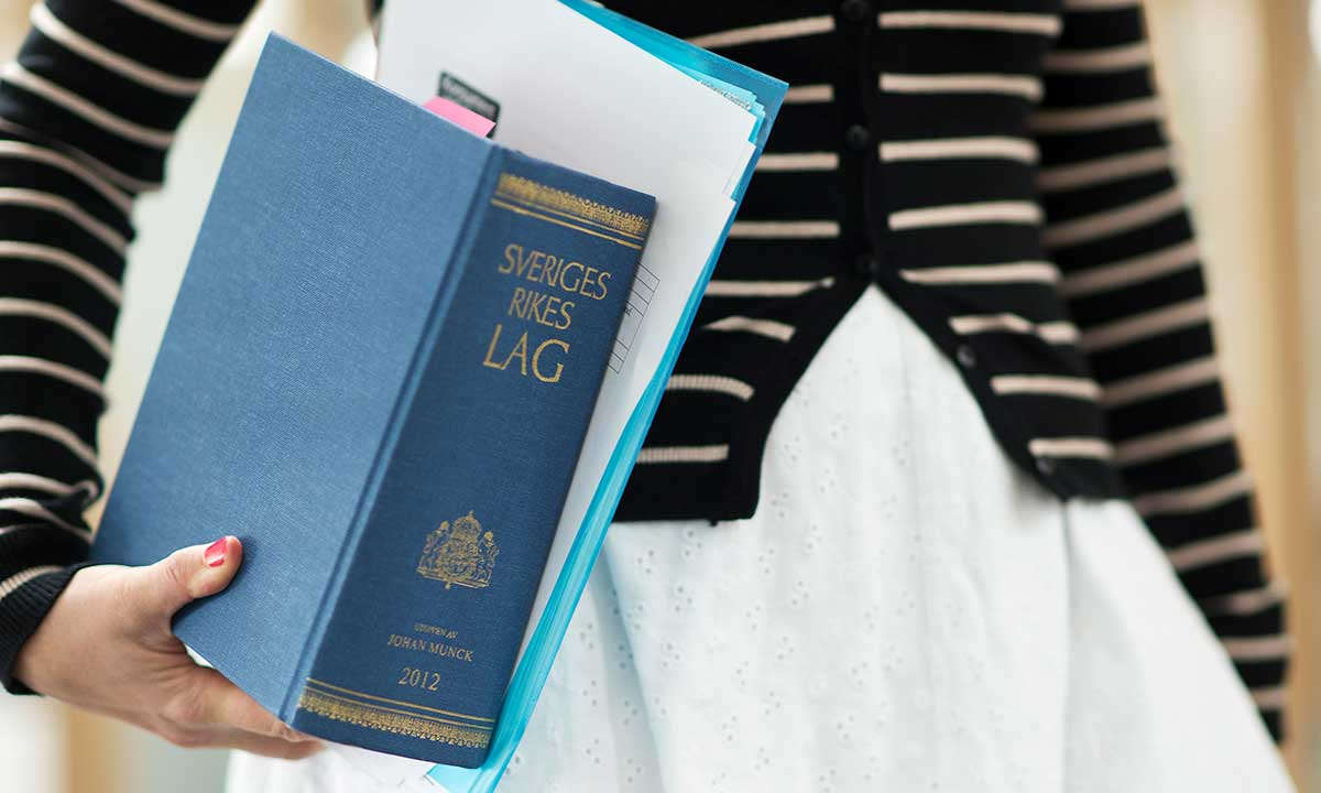 En kvinna har ett exemplar av boken Sveriges rikes lag under armen.