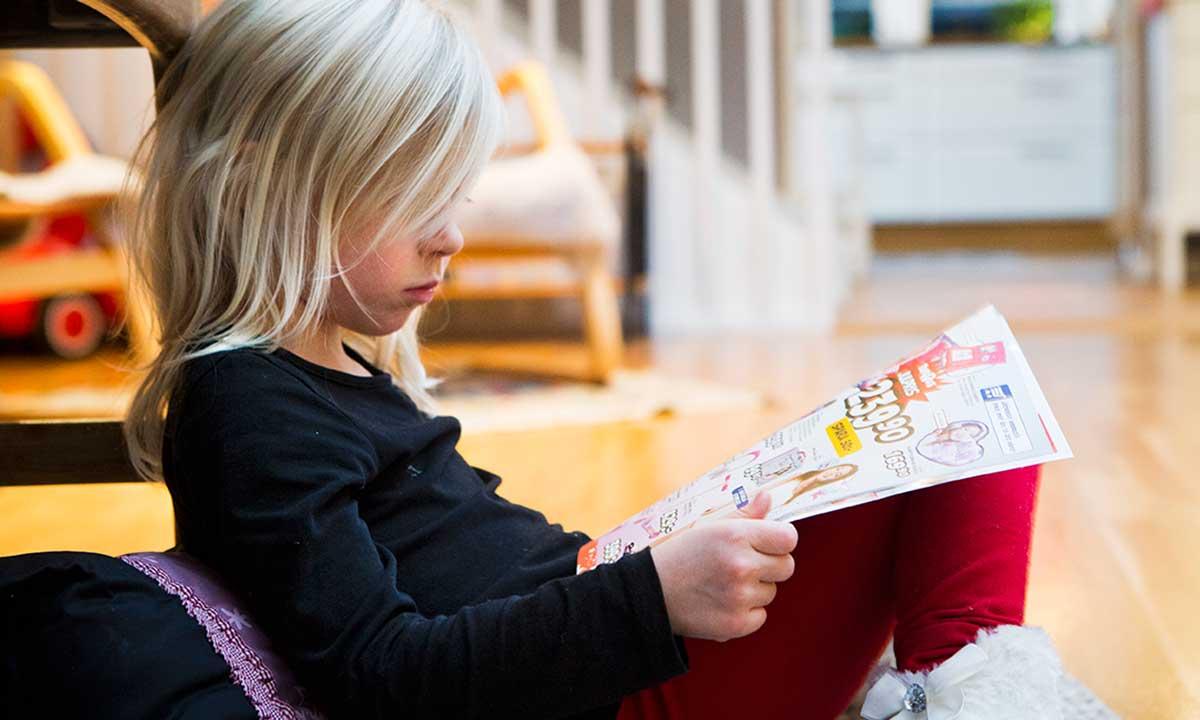 Barn sitter i en soffa och tittar i en tidning med annonser.