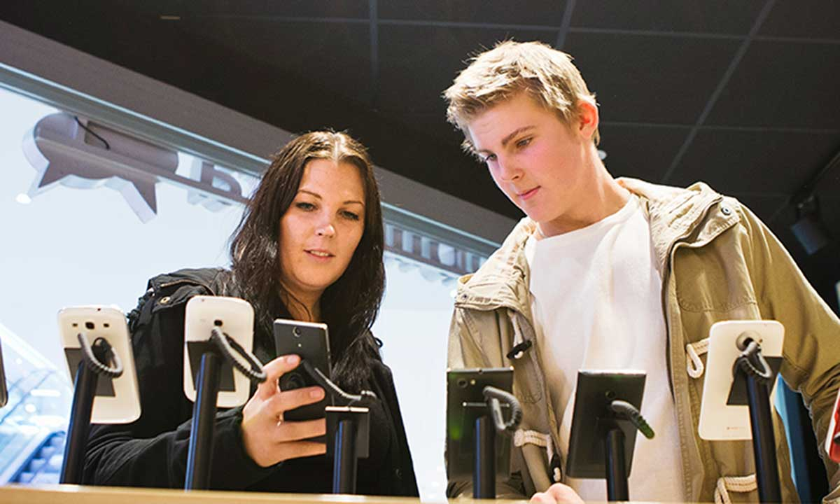 Tjej och kille tittar på mobiler i en butik.