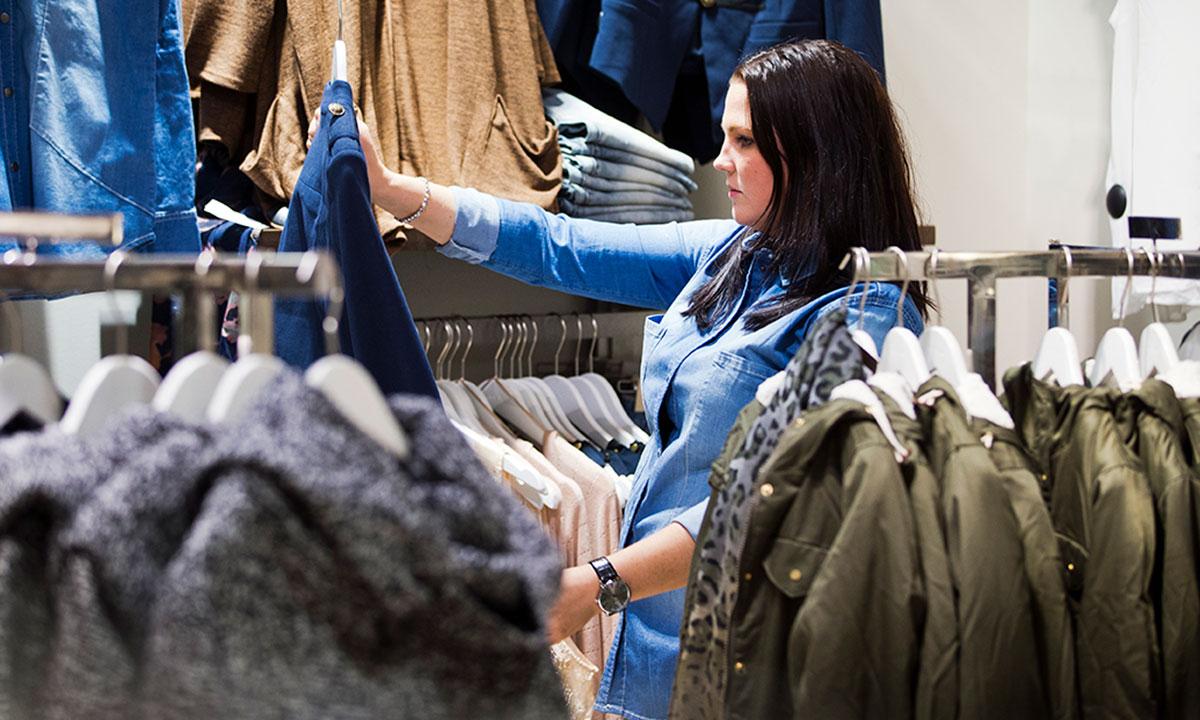 Tjej tittar på kläder i en affär.